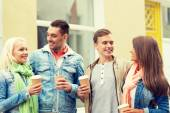Group of smiling friends with take away coffee — Stock Photo