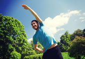 Smiling man stretching outdoors — Stock Photo