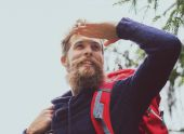 Smiling man with beard and backpack hiking — Stock Photo