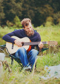Smiling man with guitar and dixie in camping — Stockfoto