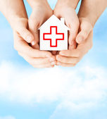 Handen met papier huis met Rode Kruis — Stockfoto