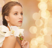 Beautiful young woman with orchid flowers — Stock Photo
