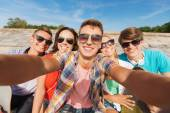 Group of smiling friends making selfie outdoors — Stock Photo