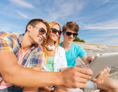 Groep lachende vrienden met tablet pc buitenshuis — Stockfoto