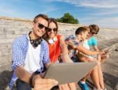 Группа улыбающихся друзей с планшетного Пк на открытом воздухе — Стоковое фото