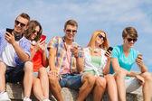 Groep lachende vrienden met smartphones outdoors — Stockfoto