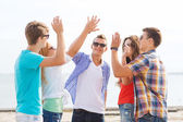 Group of smiling friends making high five outdoors — Zdjęcie stockowe