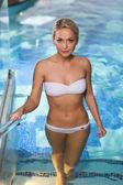 Gelukkige vrouw verhogen boven in zwembad — Stockfoto