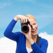 Smiling woman taking picture with digital camera — Stock Photo #61818693