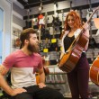Couple of musicians with guitar at music store — Stock Photo #61819469