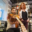 Couple of musicians with guitar at music store — Stock Photo #61819495