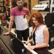 Man and woman playing piano at music store — Stock Photo #61819725