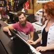 Man and woman playing piano at music store — Stock Photo #61819739
