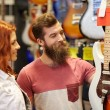 Couple of musicians with guitar at music store — Stock Photo #61819789
