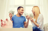 Couple with money and piggybank ot table at home — Stock Photo