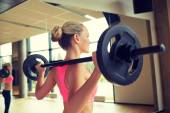 Sporty woman exercising with barbell in gym — Stock Photo