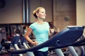Smiling woman exercising on treadmill in gym — Stock Photo