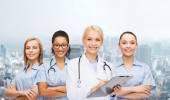 Smiling female doctor and nurses with stethoscope — Stock Photo