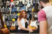 Assistant showing customer guitar at music store — Stockfoto
