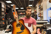 Assistant or customer with guitar at music store — Stockfoto