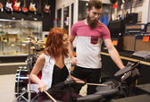 Man and woman with drum kit at music store — Стоковое фото