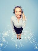 Friendly female helpline operator with headphones — Stock Photo