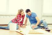 Smiling couple smearing wallpaper with glue — Stock Photo