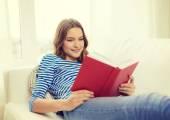 Glimlachend tienermeisje leesboek op Bank — Stockfoto
