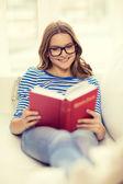 Ler tonårsflicka läsa boken på soffan — Stockfoto