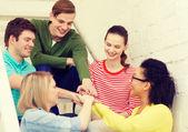 Улыбаясь студентов с руками друг на друга — Стоковое фото
