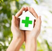 Hands holding paper house with green cross — Foto de Stock