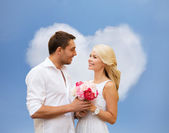 Happy couple with flowers over heart shaped cloud — Stock Photo