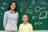 Little school girl with teacher at blackboard — Foto de Stock