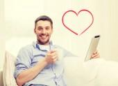 Lächelnder mann mit tabletpc zu hause arbeiten — Stockfoto