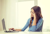 Upset teenage gitl with laptop computer at home — Stock Photo