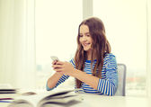 Smiling student girl with smartphone and books — Stock Photo