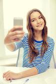 Lächelnd student mädchen mit smartphone und bücher — Stockfoto