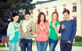 Smiling students with smartphones — Fotografia Stock