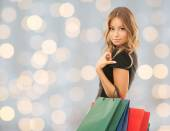 Young happy woman with shopping bags over lights — Stockfoto