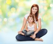Happy mother with little girl over green lights — Stock Photo