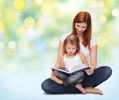 Gelukkig moeder met een schattig klein meisje en boek — Stockfoto