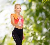 Donna sportiva sorridente con bottiglia di acqua e asciugamano — Foto Stock