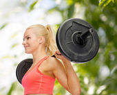 Smiling sporty woman exercising with barbell — Стоковое фото