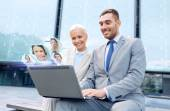 Smiling businesspeople with laptop outdoors — Stock Photo