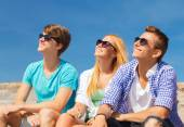 Groep lachende vrienden zittend op stad straat — Stockfoto