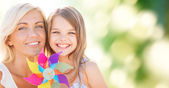 Happy mother and little girl with pinwheel toy — Stock Photo