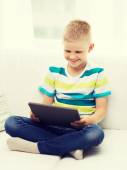 Smiling boy with tablet computer at home — Stock Photo