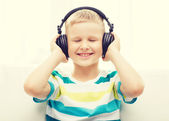 Smiling little boy with headphones at home — Stock Photo