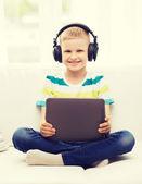 Kleiner junge mit tabletpc und kopfhörer zu hause — Stockfoto