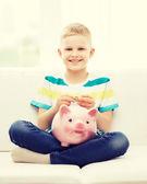 Lächelnd kleiner junge mit sparschwein und geld — Stockfoto